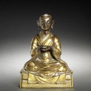 Figura de bronce dorado de un monje